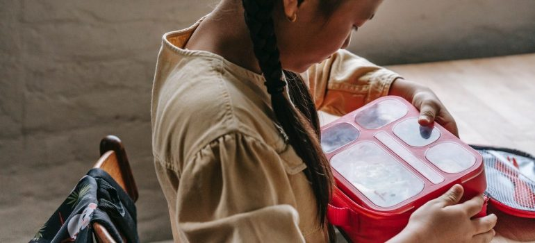 a woman packing items in her plastic container to protect stored items from bugs