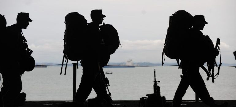three soldiers with backpacks