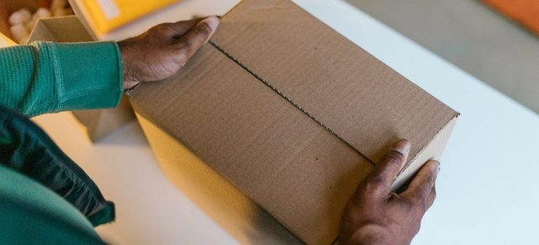a black man holding a cardboard box