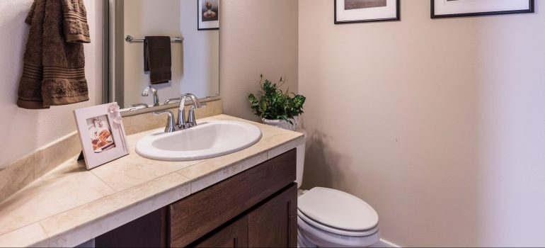 a small bathroom with a cabinet below the sink