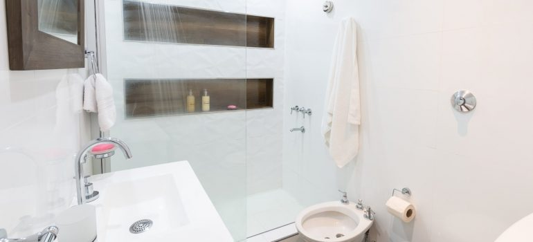 a white bathroom with a shower, a sink and a toilet