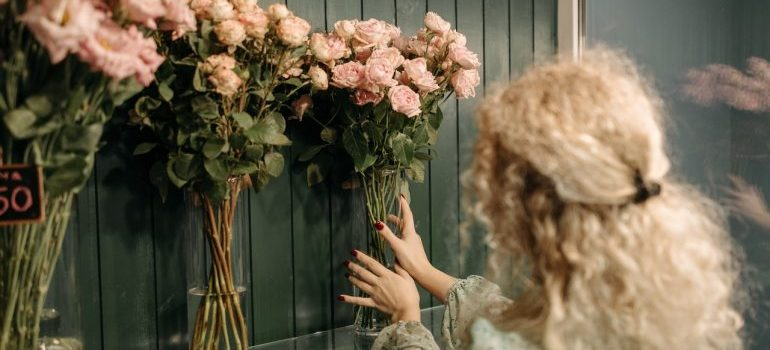 Blond woman with curly hair putting up a vase with flowers on the shelf.