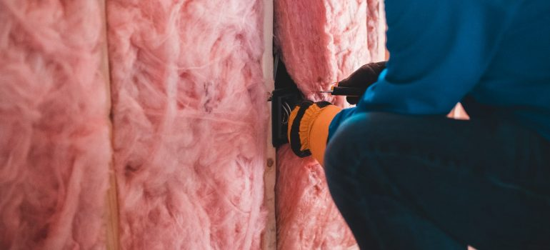 a man placing insulation into the walls of a home