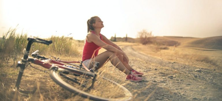 a woman resting on the side of the road with her bike beside her