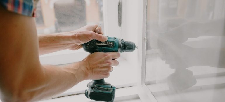 a man fixing a window as one of the ways to prep your new home for summer weather