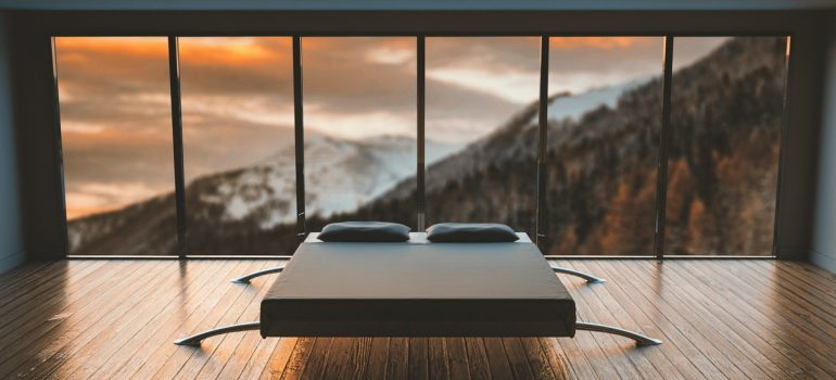 a large bed in an empty room with an open view window behind it