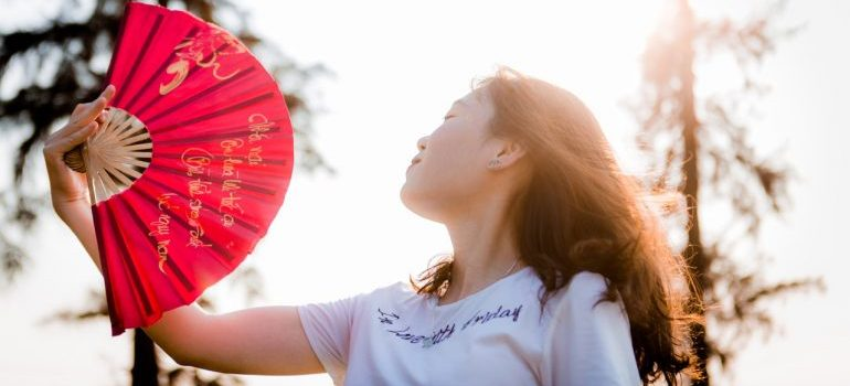 A woman fanning herself during a move because she knows that one of the best ideas to make your summer move cooler is to keep yourself cool.