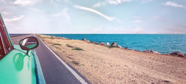 a view of an ocean from a car that is driving on the road