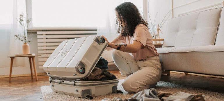 a woman packing clothes in a suitcase