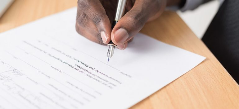 a man signing an agreement while renting a storage unit in Philadelphia