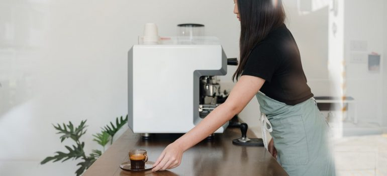 a woman barista placing a coffee cup on the counter