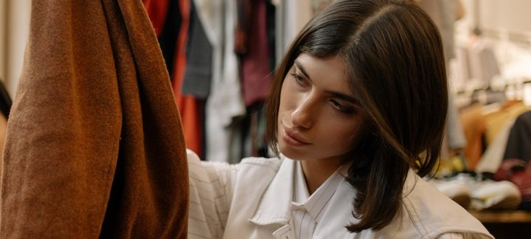 a woman inspecting a brow leather coat
