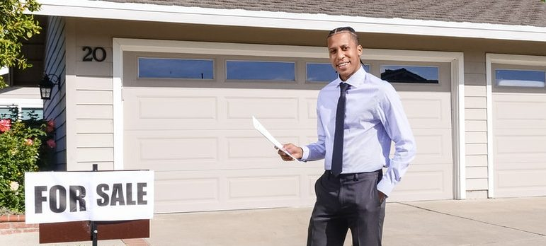 Realtor in front of a suburban home