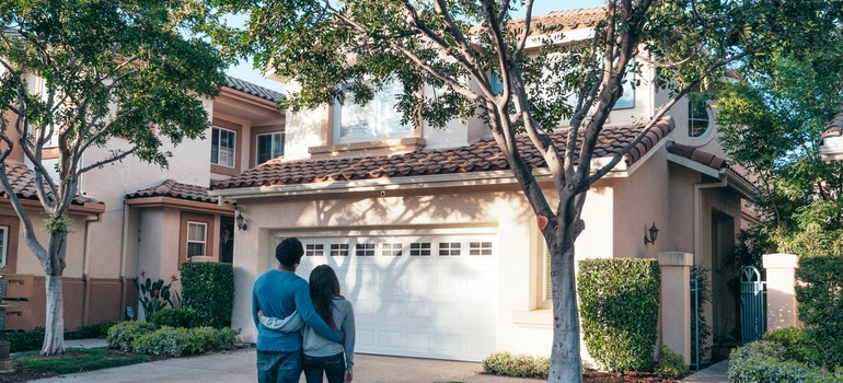 The couple stands in front of the property before buying their first home in Media PA