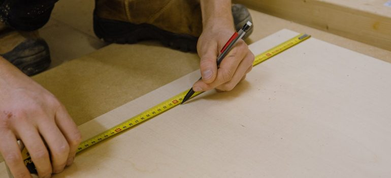 a man measuring the dimensions on the floor