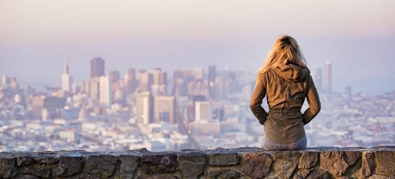 Girl sitting and looking at the panorama of her city