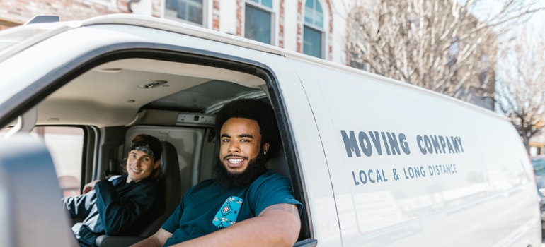 two professional movers in a van, ready for packing and moving fragile items to Downingtown