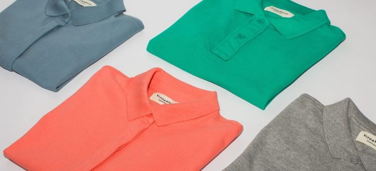 Four diffrent color shirts folded on a bed